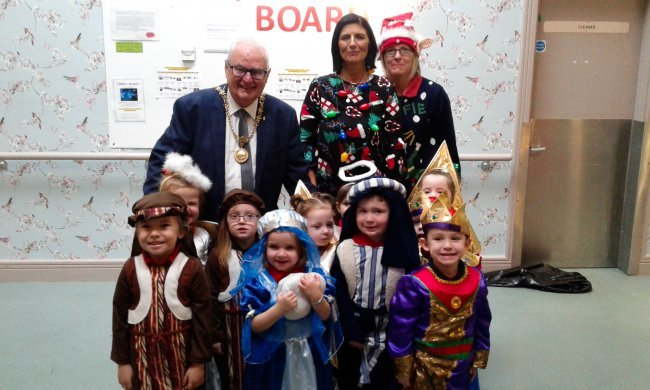 High Sheriff, Tommy Sandford, visits Clifton Nursing Home to watch Tudor Lodge Nursery perform Christmas songs.