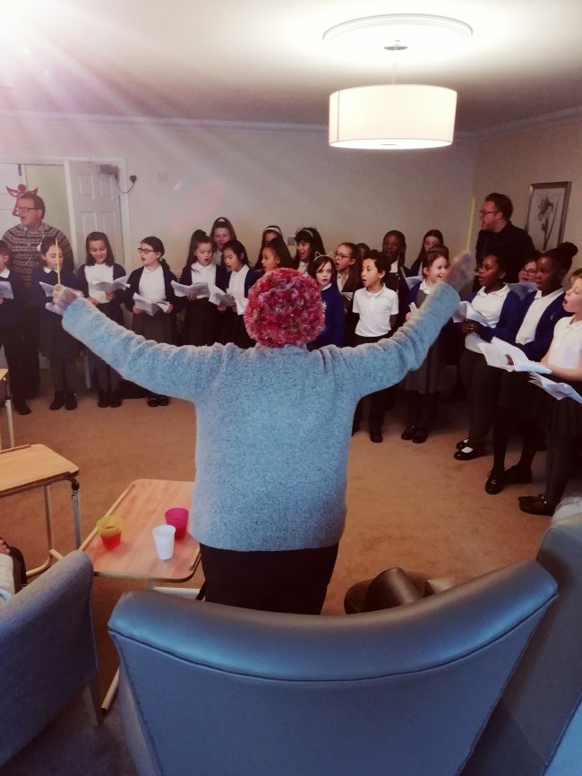 Residents at Kathryn Court in Essex are visited by local school choir.
