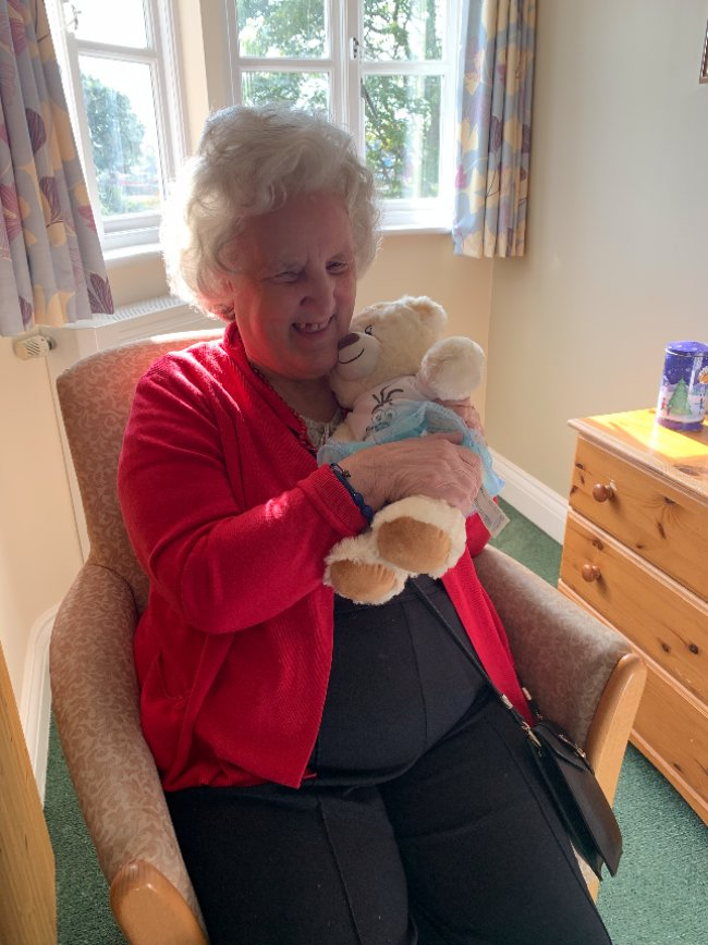 Resident at Broomhills in Essex gets teddy bear for person-centred care assistance.