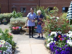 Resident takes a walk through the garden with one of our experienced carers