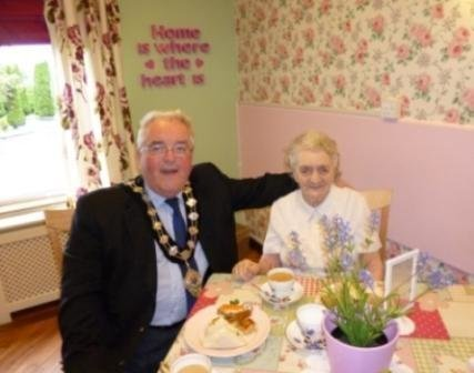 Alderman McAvoy having tea with a resident